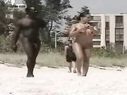 Naakt vrouwelijk naakt met een zwarte man gefilmd op het strand