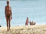 Een rijpe vrouw topless op het strand