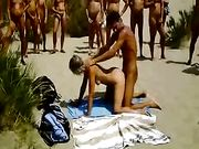 Paar maakt de geslacht op een strand met publiek