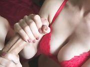 Een vriendin met grote tieten met behulp van haar handen om het sperma te krijgen