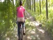 Naakt buiten op de fiets in het bos