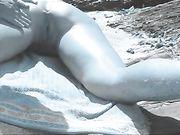 Vinger in de ezel van vrouw op het nudist strand