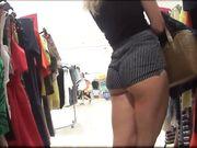 Een verborgen camera in de winkel met een sexy vrouw in strakke shorts