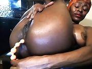 Een naakte zwarte vrouw voor de webcam met een dildo in haar kont