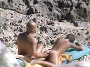 Een naakte moeder wordt gefilmd op het strand